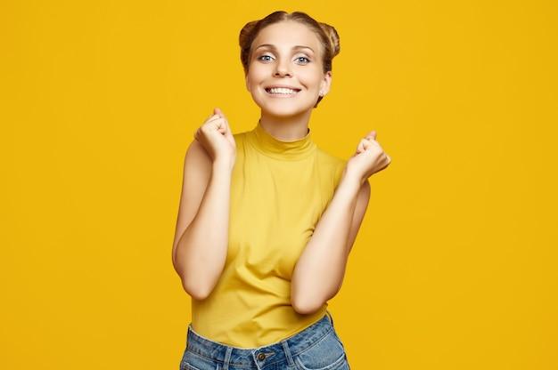 Positieve portret van prachtige blonde hipster vrouw model met krullend haar poseren op kleurrijke gele achtergrond in de studio