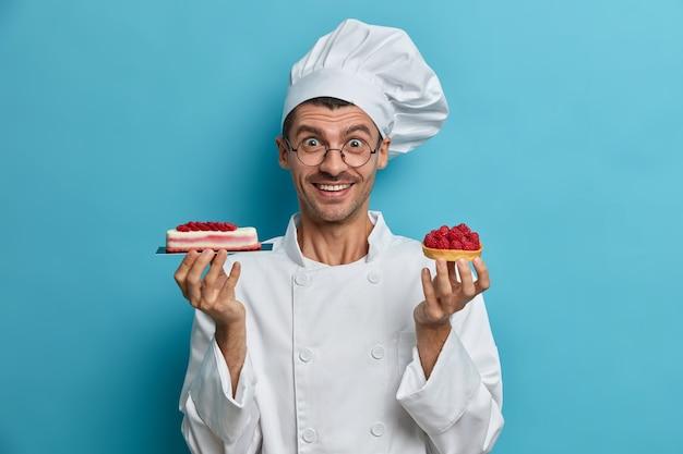 Positieve professionele banketbakker houdt smakelijke handgemaakte desserts met bessen