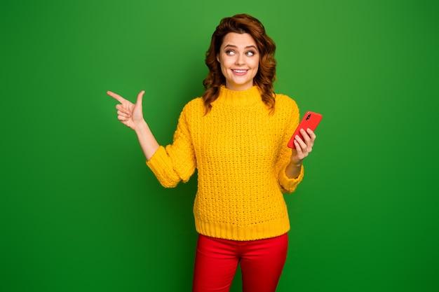 Positieve promotor vrouw punt wijsvinger copyspace gebruik mobiele telefoon aanwezig sociaal netwerk advertenties promo direct manier dragen stijlvol trui broek geïsoleerd helder glans kleur muur