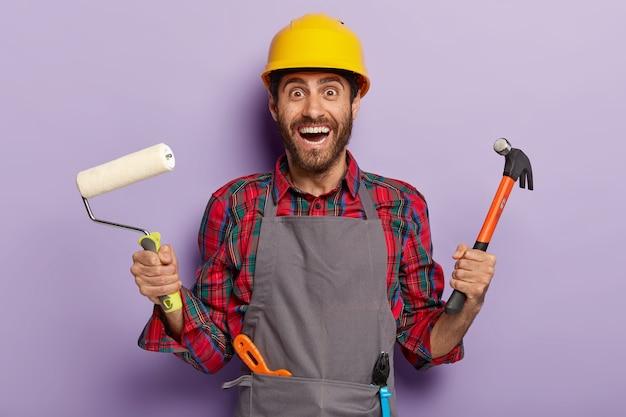 Positieve reparateur houdt hamer en verfroller vast, draagt een schort en veiligheidshelm, heeft veel bouwgereedschap, klaar voor huisrenovatie. een gelukkige professionele serviceman kan alles in uw appartement repareren