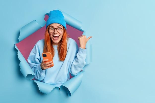 Positieve roodharige jonge vrouw met vrolijke uitdrukking wijst op kopie ruimte door papiergat.