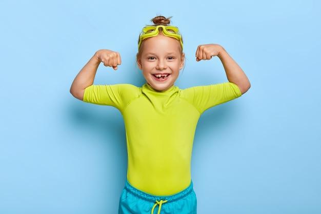 Positieve roodharige meisje poseren in haar zwembad outfit
