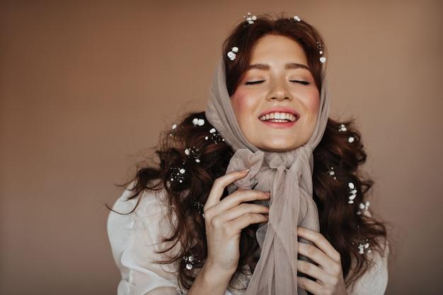 Positieve roodharige vrouw lacht met gesloten ogen. portret van vrouw in beige sjaal en met witte bloemen in haar haar.