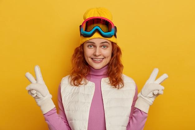 Positieve roodharige vrouw met blije uitdrukking, maakt vredesgebaar met beide handen, gelukkig glimlacht en vormt tegen gele achtergrond.