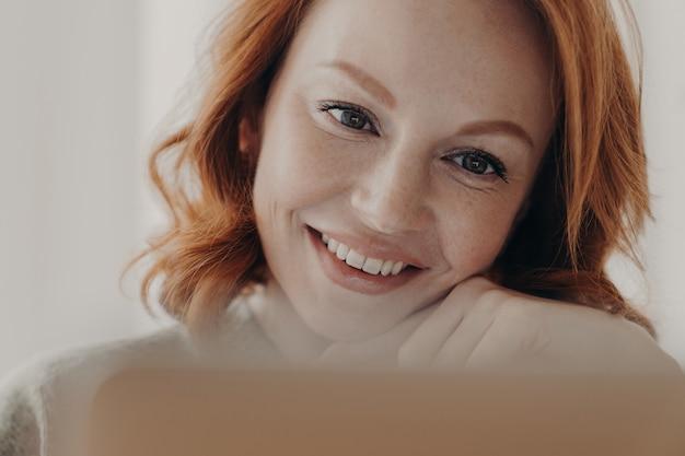 Positieve roodharige vrouw met sproeten huid en brede glimlach, geconcentreerd op laptopcomputer