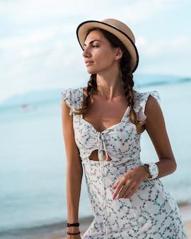 Positieve rustige vrouw in lichte zomerjurk, strooien hoed, tropische locatie