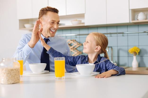 Positieve schattig leuk meisje kijkt naar haar vader en geeft hem high five tijdens het ontbijt met hem