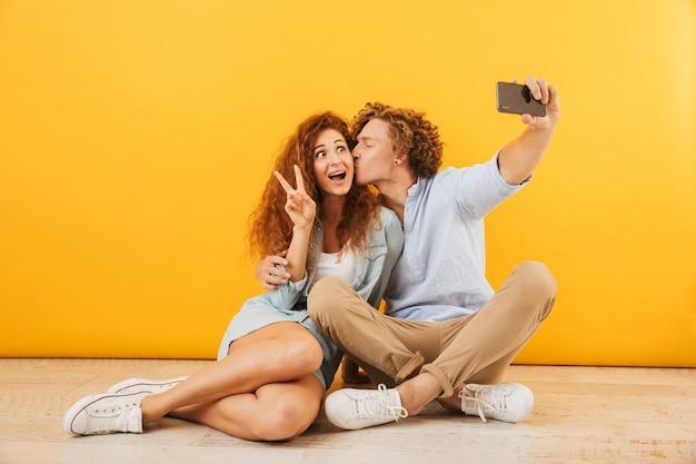 Positieve schattige mensen man en vrouw samen op de vloer zitten en vredesteken tonen terwijl het nemen van selfie op smartphone, geïsoleerd op gele achtergrond