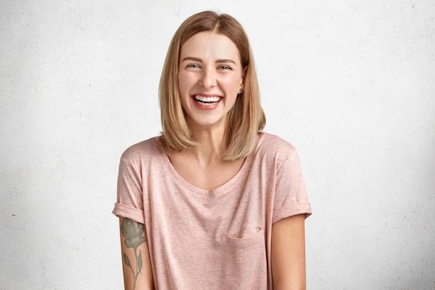 Positieve schattige vrouw met kortgeknipt kapsel, lacht zachtjes naar de camera, heeft een getatoeëerde arm en een gezonde huid, in een goed humeur na een buitenwandeling