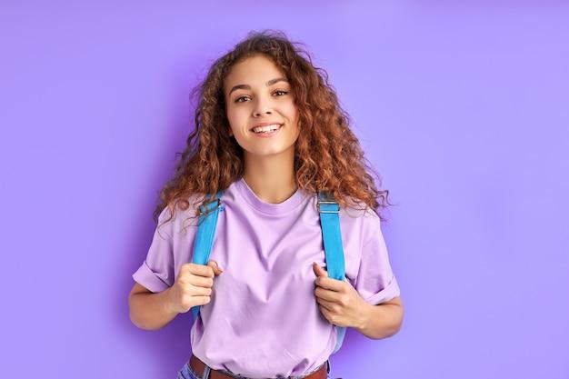Positieve school meisje met tas poseren op camera geïsoleerd op paarse achtergrond