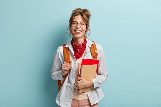 Positieve schoolmeisje draagt spiraal blocnote, notebook, draagt rugzak, klaar voor school en lessen