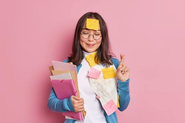 Positieve schoolmeisje kruist vingers gelooft in geluk op examen draagt ronde bril geplakt met papieren en plakbriefjes geschreven informatie om te onthouden maakt wieg. student gebruikt spiekbriefjes.