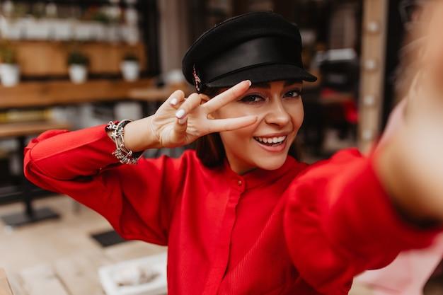 Positieve selfie van helder lachende jonge dame met mooie ogen, goede manicure, prachtige make-up in een mooie zijden jurk met zwarte band. model toont vredesteken met haar vingers
