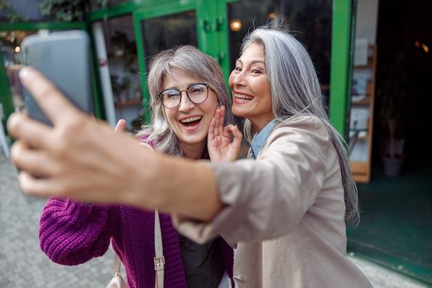 Positieve senior aziatische dame met grijsharige vriend neemt selfie op moderne stadsstraat