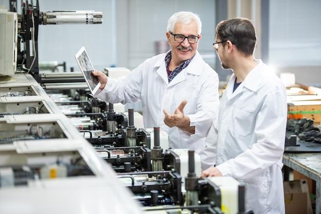 Positieve senior inspecteur in laboratoriumjas in gesprek met collega tijdens het gebruik van tablet om de afdrukkwaliteit te analyseren