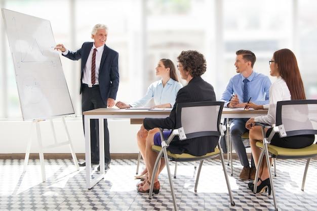 Positieve senior leader tekening grafiek op vergadering