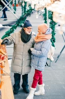 Positieve senior man die op winterdag met zijn opgewonden vrouw staat en naar de bakkerij wijst op een toonbank op de beurs