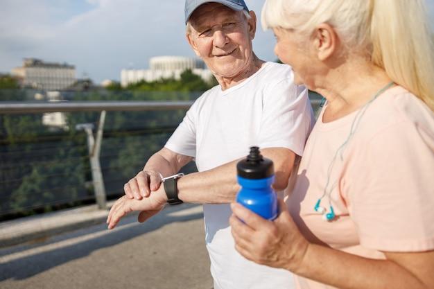 Positieve senior man met smartwatch kijkt naar blonde vrouw die samen traint op voetgangersbrug