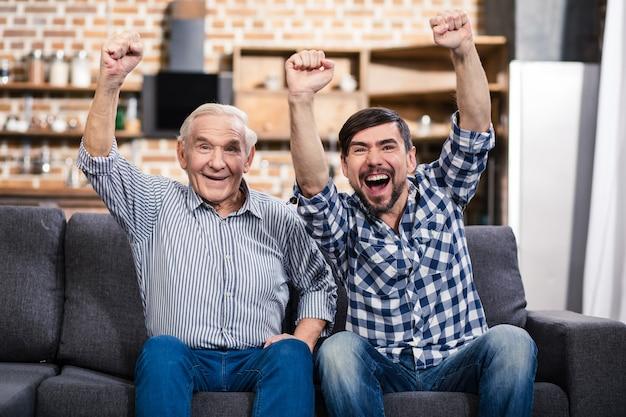 Positieve senior man zittend op de bank met zijn zoon tijdens het kijken naar voetbal