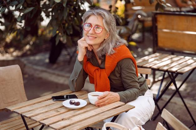 Positieve senior vrouw met bril en kopje koffie aan tafel op terras in openlucht