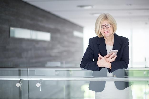 Positieve senior zakenvrouw bedrijf mobiele telefoon