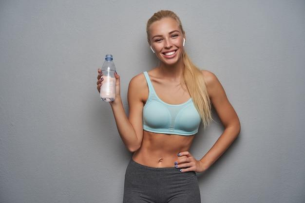 Positieve slanke jonge blonde vrouw met casual kapsel poseren over de lichtgrijze achtergrond met fles water, in hoge geest zijn en vreugdevol glimlachen naar de camera