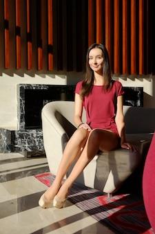 Positieve slanke vrouw met lange benen in beige panty's en stiletto's in de lobby