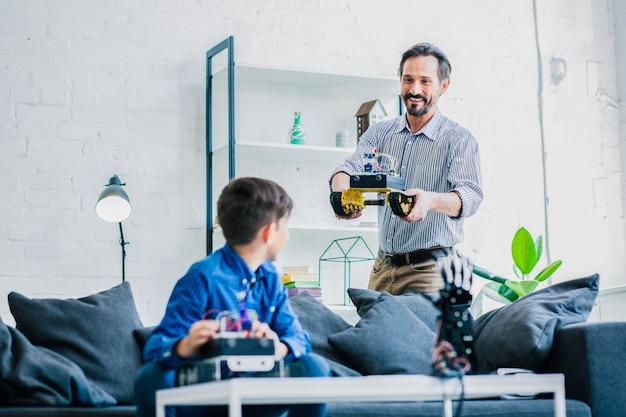Positieve slimme man die zijn robot vasthoudt terwijl hij hem aan zijn zoon laat zien en samen aan een technisch project werkt