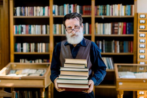 Positieve slimme oude bebaarde man in donker overhemd en leren vest, bibliotheekmedewerker, leraar, werken in bibliotheek, stapel boeken houden terwijl je over boekenplanken achtergrond