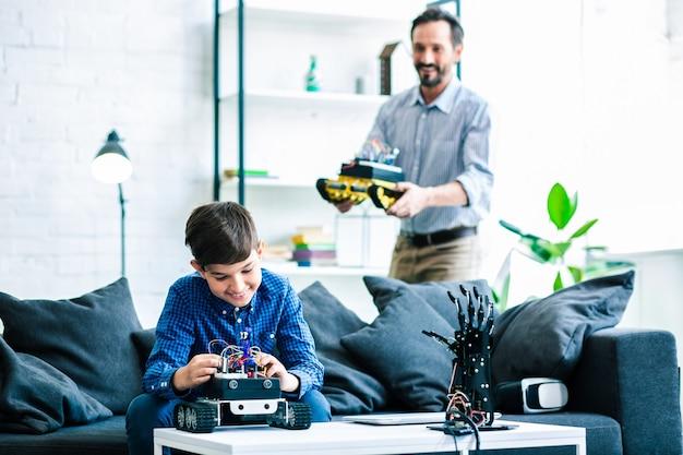 Positieve slimme schooljongen die zijn robotapparaat bouwt terwijl zijn vader op de achtergrond staat