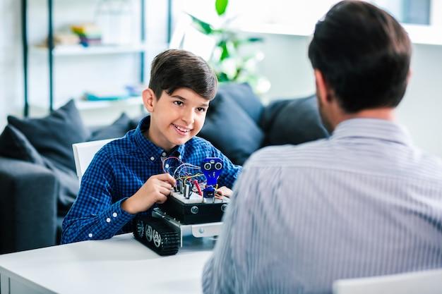 Positieve slimme schooljongen die zijn robotapparaat test terwijl hij bij zijn vader rust