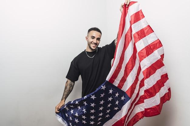 Positieve spaanse man met getatoeëerde armen poseren met een amerikaanse vlag geïsoleerd op een witte muur