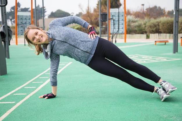 Positieve sportieve meisje training kern spieren