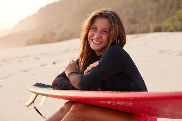 Positieve sportieve vrouw met brede glimlach, heeft een ontspannen uitdrukking, is in hoge geest, poseert op de kustlijn