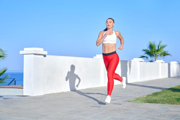 Positieve sportieve vrouw op een zomerochtend joggen op de strandweg in rode beenkappen op de achtergrond van de zeekust