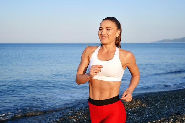 Positieve sportieve vrouw op een zomerochtend joggen op het strand in rode legging op de achtergrond van de zeekust dichtbij uo