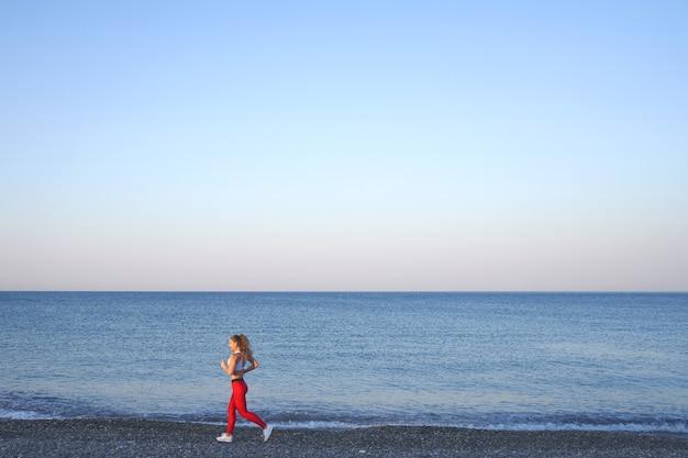 Positieve sportieve vrouw op een zomerochtend joggen op het strand in rode legging op de achtergrond van de zeekust