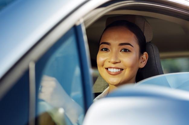 Positieve stemming. aangename aardige vrouw lachend tijdens het autorijden