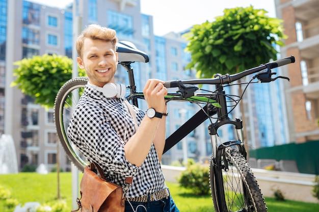 Positieve stemming. blije aardige man die naar je glimlacht terwijl hij zijn fiets draagt