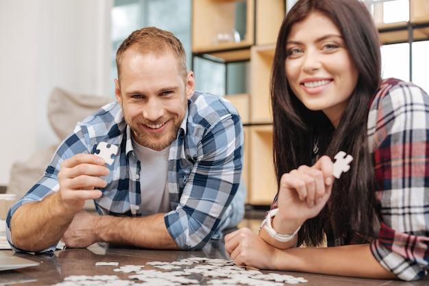 Positieve stemming. blije gelukkige jonge mensen glimlachen en kijken naar je terwijl je de puzzel doet