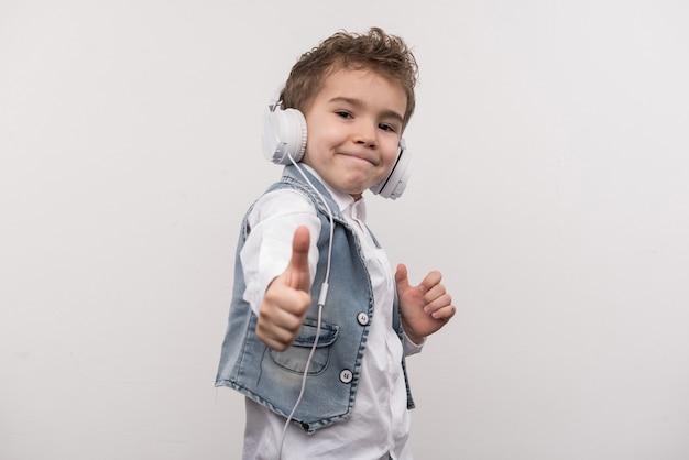 Positieve stemming. blije positieve jongen die ok teken toont terwijl het dragen van hoofdtelefoons