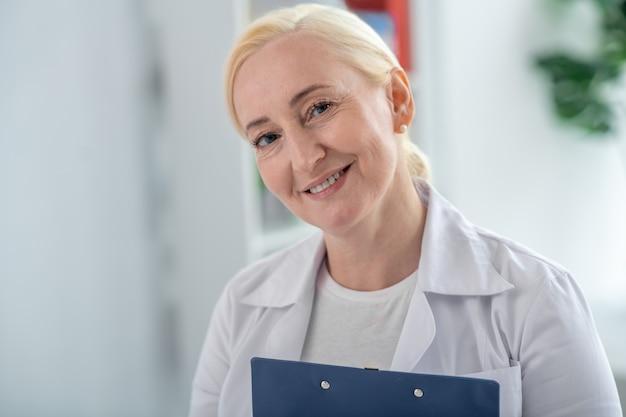Positieve stemming. blonde en arts die op middelbare leeftijd positief glimlacht kijkt