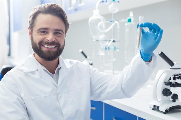 Positieve stemming. gelukkige aardige succesvolle bioloog die een reageerbuis vasthoudt en glimlacht terwijl hij naar jou kijkt