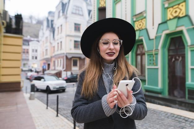 Positieve, stijlvolle vrouw luistert naar muziek, kijkt in de telefoon en lacht tegen de achtergrond van de straat