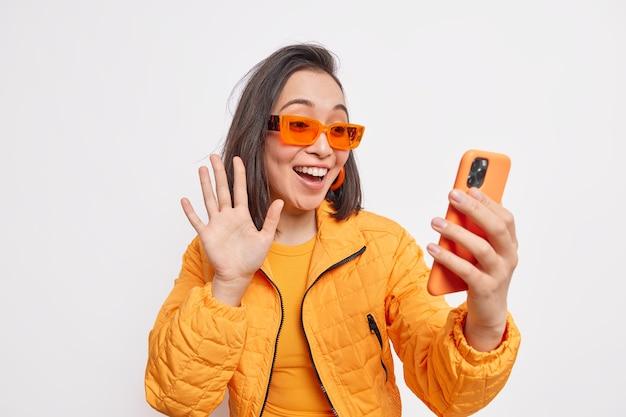 Positieve stijlvolle vrouwelijke blogger zwaait hallo naar volgers in sociale netwerken draagt oranje jas en zonnebril maakt begroetingsgebaar op smartphone geïsoleerd over witte muur maakt verbinding met chat van vrienden