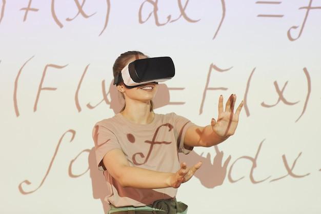 Positieve student meisje in vr-bril gebaren handen tijdens het oplossen van wiskundeprobleem, ze geniet van virtueel onderwijs