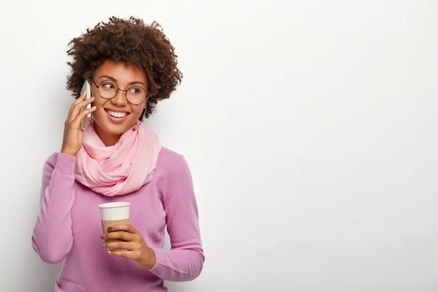 Positieve student praat met interesse en vreugde via mobiel, voelt zich verlegen om een compliment te ontvangen, draagt zijden sjaal en paarse coltrui, drinkt graag aromatische espresso