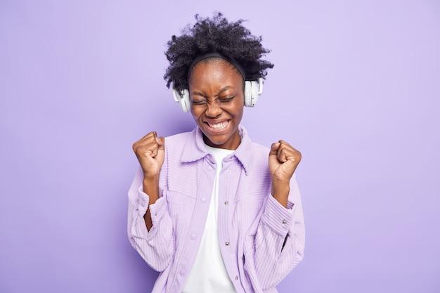 Positieve succesvolle afro-amerikaanse vrouw balt vuisten van vreugde luistert naar nieuwe muziekafspeellijst via draadloze koptelefoon