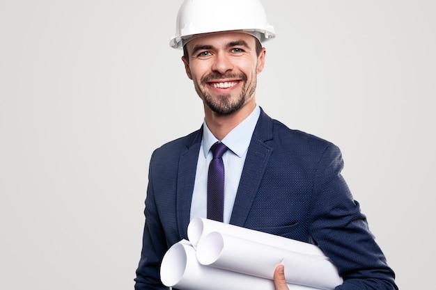 Positieve succesvolle professionele mannelijke ingenieur in formele pak en bouwvakker met opgerolde blauwdrukken in de hand kijken