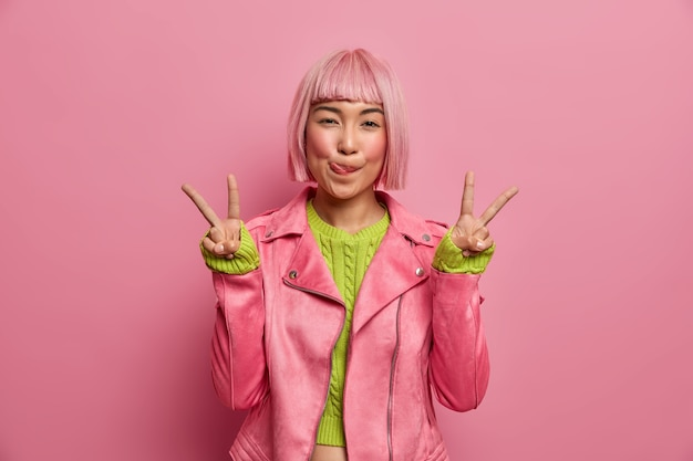 Positieve succesvolle roze harige aziatische vrouw likt lippen, maakt gebaar van overwinning, toont twee vingers, gekleed in een stijlvolle jas, vormt binnen